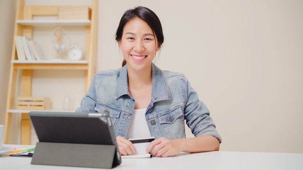 Piękna azjatycka kobieta używa pastylkę kupuje online zakupy kredytową kartą podczas gdy jest ubranym przypadkowego obsiadanie na biurku w żywym pokoju w domu.