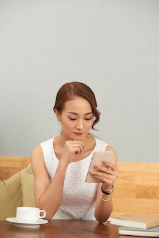 Piękna azjatycka kobieta używa smartphone w domu