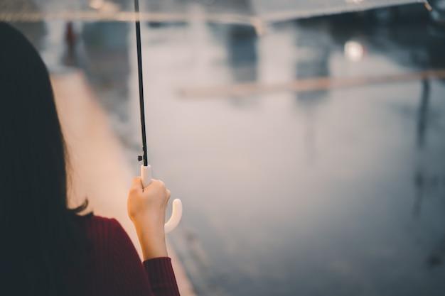 Piękna azjatycka kobieta w czerwonym swetrze stojąc przy drodze podczas deszczu i trzymając parasol