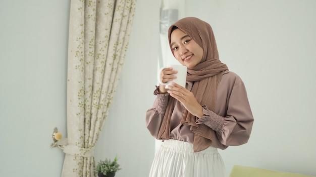 Piękna azjatycka kobieta w hidżabie uśmiecha się, stojąc, delektując się drinkiem w domu