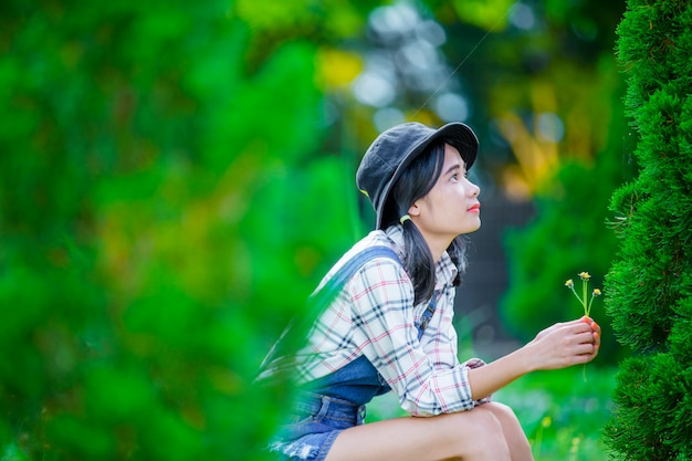 Piękna azjatycka kobieta w kapeluszu, aby zrelaksować się i cieszyć się w zielonym ogrodzie jako tło.