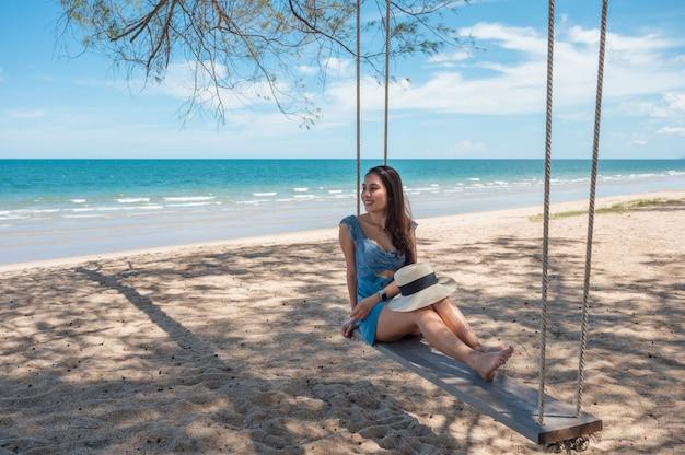 Piękna azjatycka kobieta w kapeluszu siedzi przy drewnianej huśtawce na plaży w tropikalnym morzu