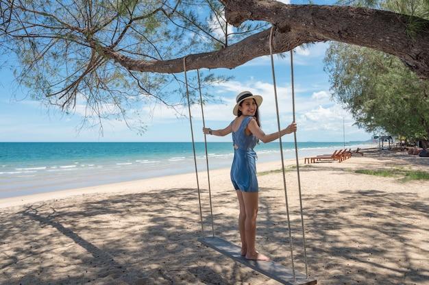 Piękna azjatycka kobieta w kapeluszu stojąca przy drewnianej huśtawce na plaży w tropikalnym morzu