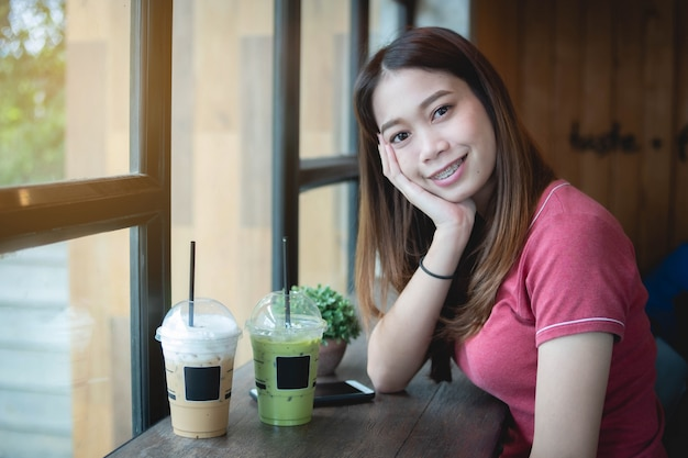 Piękna azjatycka kobieta w kawiarni, patrzejący kamerę, z mrożonym cappuccino i zieloną herbatą matcha