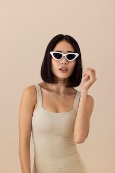 Piękna azjatycka kobieta w okularach przeciwsłonecznych pozuje