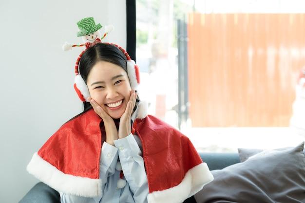 Piękna azjatycka kobieta w stroju santa siedzi na kanapie