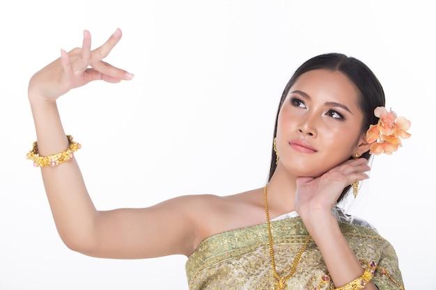 Piękna azjatycka kobieta w tajskiej tradycyjnej sukni ślubnej z pięknym kwiatem