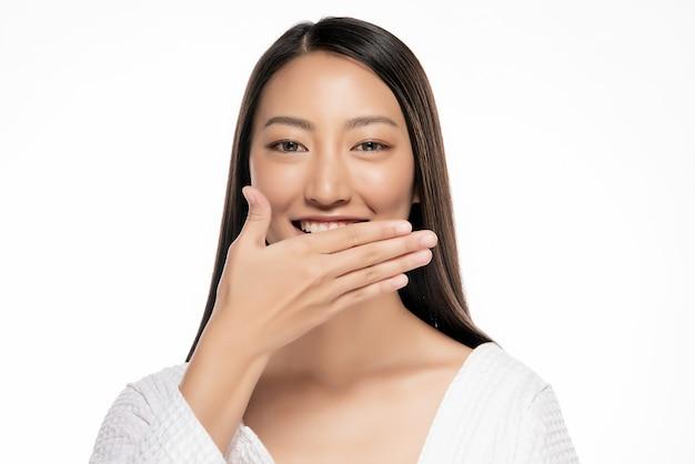 Piękna azjatycka kobieta wręcza knebel na białym blackground.