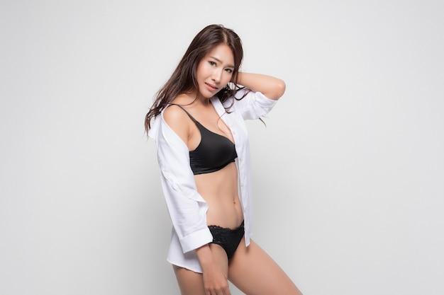 Piękna azjatycka kobieta z długimi brązowymi włosami ubrana w białą koszulę i czarny biustonosz, seksowna pozycja mody na szarej powierzchni