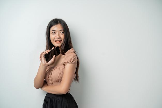 Piękna azjatycka kobieta z długimi włosami czuje się bardzo szczęśliwa, gdy trzyma inteligentny telefon