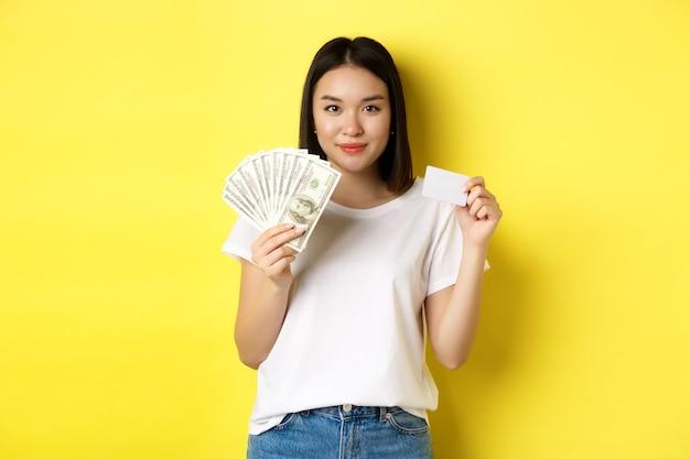 Piękna azjatycka kobieta z krótkimi ciemnymi włosami, ubrana w białą koszulkę, pokazująca pieniądze w dolarach i plastikową kartę kredytową, stojąca na żółtym tle.