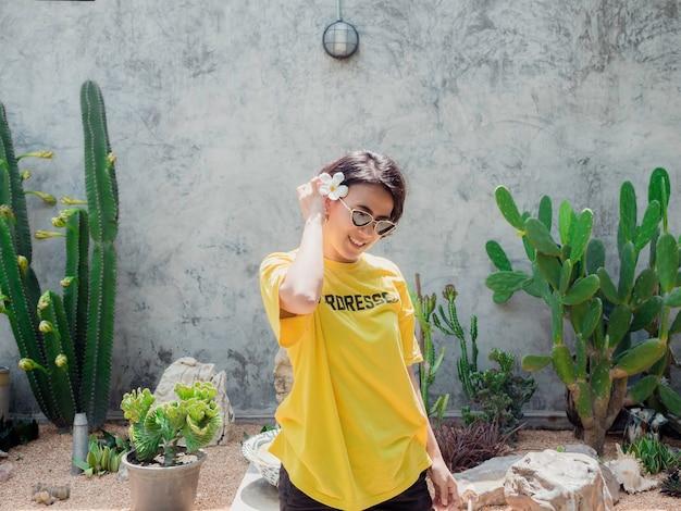 Piękna azjatycka kobieta z krótkimi włosami, nosząca okulary przeciwsłoneczne i żółtą koszulę na szarym tle
