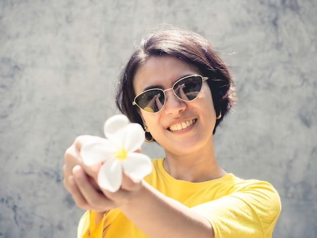 Piękna azjatycka kobieta z krótkimi włosami, nosząca okulary przeciwsłoneczne i żółtą koszulę z białym kwiatem