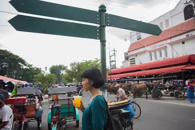 Piękna azjatycka kobieta z kubkiem napoju na ulicy