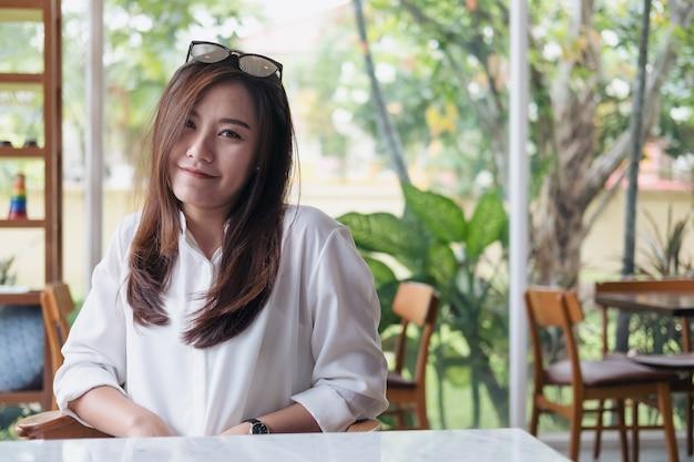 Piękna azjatycka kobieta z smiley twarzą i uczucie dobrym obsiadaniem w kawiarni z zieloną naturą