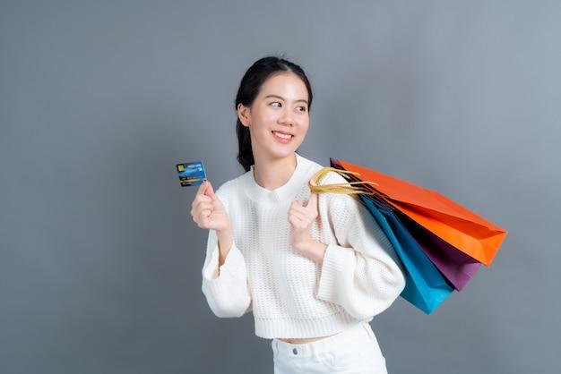 Piękna azjatycka kobieta z torby na zakupy i pokazując kartę kredytową na białym tle na szarej ścianie
