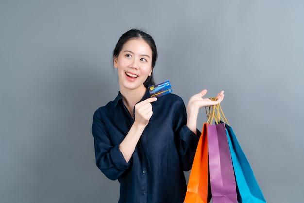 Piękna azjatycka kobieta z torby na zakupy i pokazując kartę kredytową na białym tle