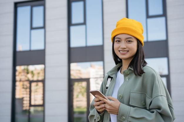 Piękna azjatycka kobieta za pomocą telefonu komórkowego zakupy online