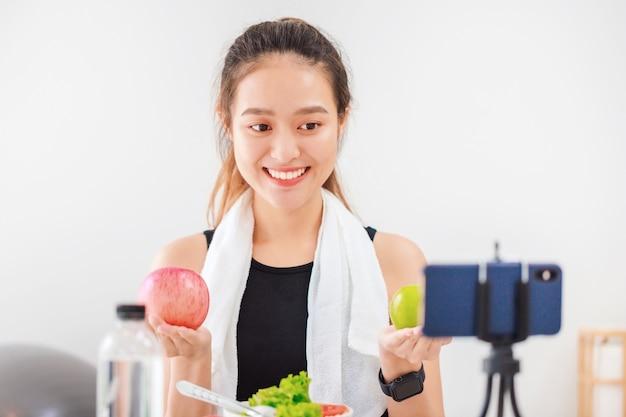 Piękna azjatycka kobieta zdrowa blogerka pokazuje owoce jabłka i czystą dietę. przed smartfonem do nagrywania wideo vlog na żywo w domu. wpływowy fitness w mediach społecznościowych online.