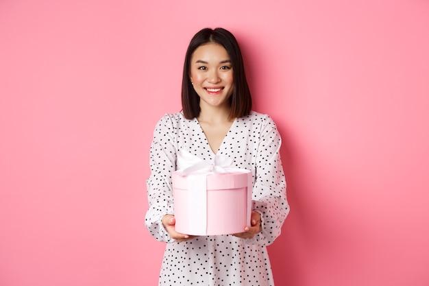 Piękna azjatycka kobieta życząca wesołych świąt, dając ci prezent w uroczym pudełku stojącym na różowym tle...
