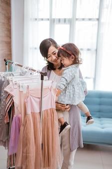 Piękna azjatycka matka zabierająca córkę na zakupy do centrum handlowego