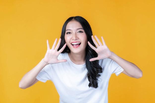 Piękna azjatycka młoda kobieta krzyczy ogłaszając dobrą wiadomość lub promocję, trzymając ręce przy twarzy z otwartymi ustami promocja wiadomości herald na białym tle na żółtym tle
