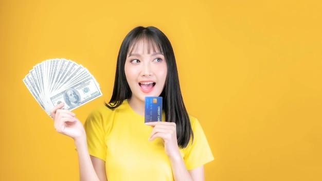 Piękna azjatycka młoda kobieta ładna dziewczyna z grzywką fryzury w żółtej koszuli, trzymając kartę kredytową i pieniądze rachunki w dolarach amerykańskich i w ręku na zakupy online zapłacić na białym tle na żółtym tle
