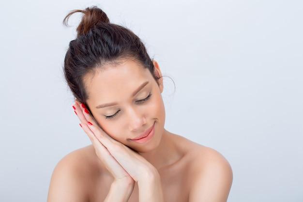 Piękna azjatycka młoda kobieta modelka z naturalnym makijażem twarzy w kształcie litery v na białym tle