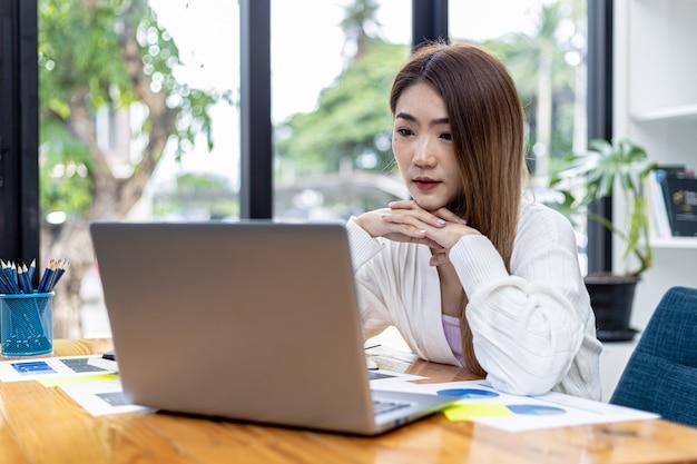 Piękna azjatycka młoda kobieta patrząc na informacje na laptopie, obraz koncepcji azjatyckiej kobiety biznesu pracy inteligentnej, nowoczesnej kobiety wykonawczej, startowej kobiety biznesu, kobiety lidera biznesu.