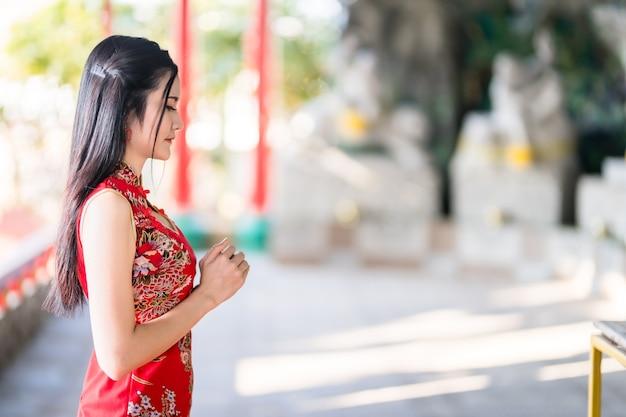 Piękna azjatycka młoda kobieta ubrana w czerwony tradycyjny chiński cheongsam, siedząca modlić się do posągu buddy na chiński nowy rok festiwal w chińskiej świątyni