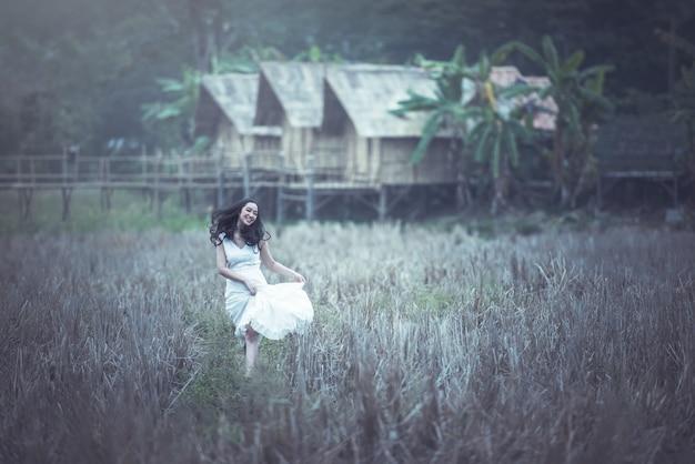 Piękna azjatycka młoda kobieta w ryżowych polach łąkowych
