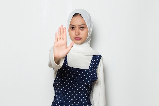 Piękna azjatycka muzułmańska kobieta pokazuje gest zatrzymania rąk