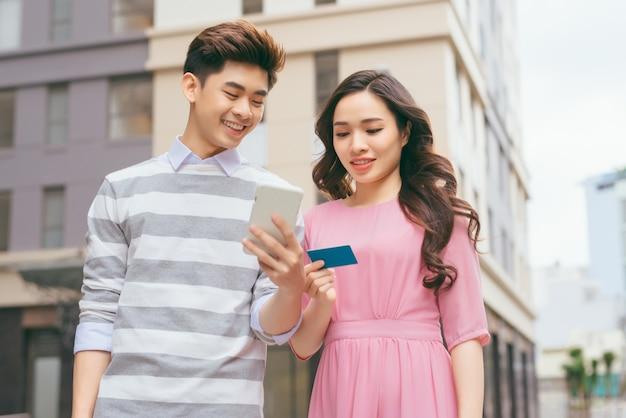 Piękna azjatycka para robi zakupy kartą kredytową w mieście