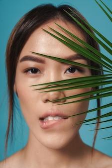 Piękna azjatycka poważna kobieta pozuje nago na białym tle nad niebieską ścianą ściana trzyma liść roślin gryźć wargę.