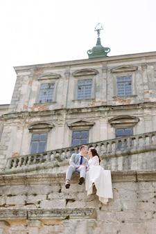 Piękna azjatycka ślub para pozuje podczas gdy siedzący na kamiennej ścianie stary zrujnowany kasztel