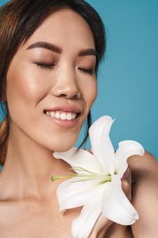 Piękna azjatycka wesoła kobieta pozowanie nago na białym tle nad niebieską ścianą ściana trzyma kwiat.