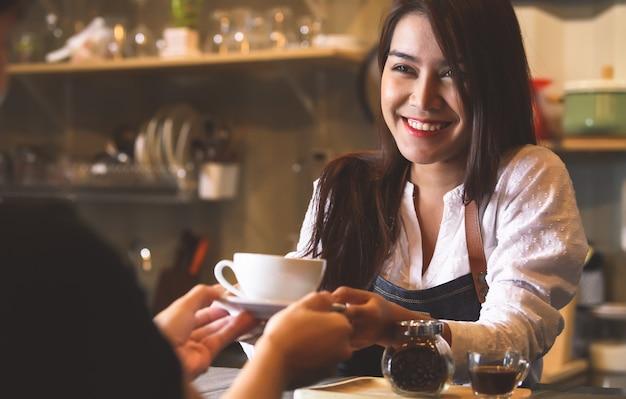 Piękna azjatycka żeńska barista słuzyć gorącą kawę klient przy kontuarem barem