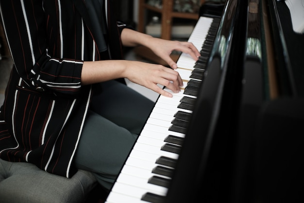 Piękna azjatykcia dziewczyna uczy się bawić się pianino.