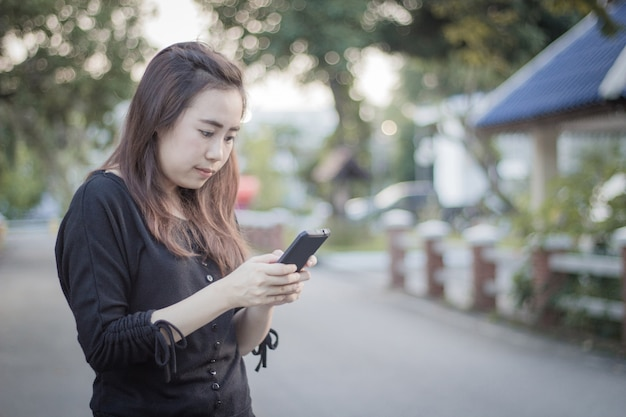 Piękna azjatykcia dziewczyna używa telefon komórkowego na drodze