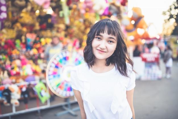 Piękna azjatykcia dziewczyna w parku rozrywki, ono uśmiecha się