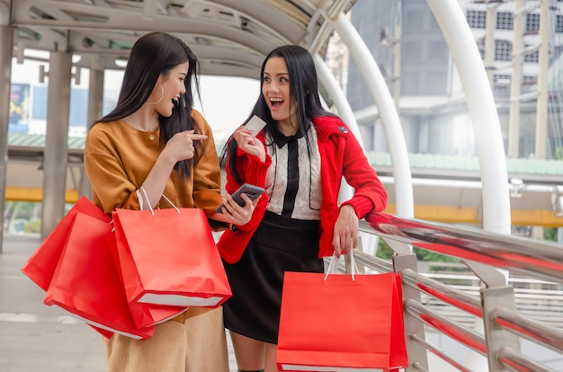 Piękna azjatykcia i caucasian młoda kobieta z mądrze telefonem, kartą kredytową i mienia torba na zakupy
