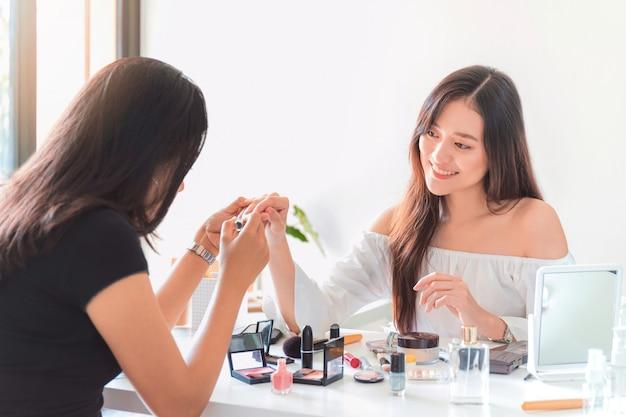 Piękna azjatykcia kobieta blogger pokazuje jak gwoździa połysk i używa kosmetyka.