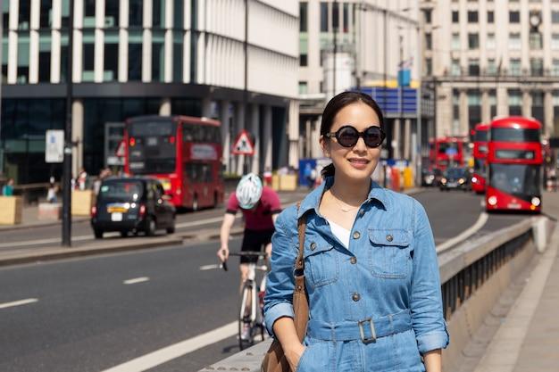 Piękna azjatykcia kobieta chodzi na london moscie z czarnymi okularami przeciwsłonecznymi.