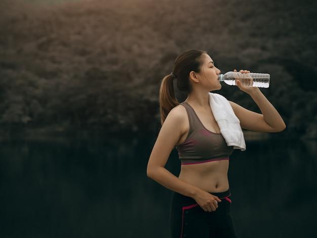 Piękna azjatykcia kobieta ćwiczy outside i pije wodę