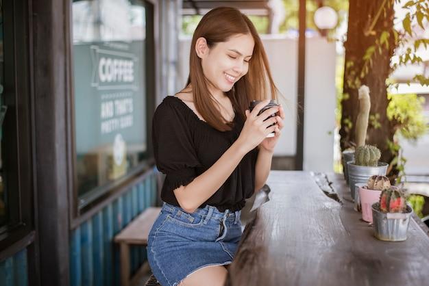 Piękna azjatykcia kobieta pije kawę