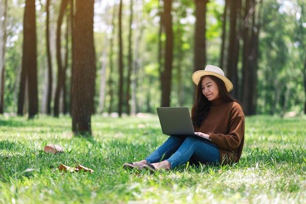 Piękna azjatykcia kobieta pracuje i pisze na klawiaturze laptopu podczas gdy siedzący w parku
