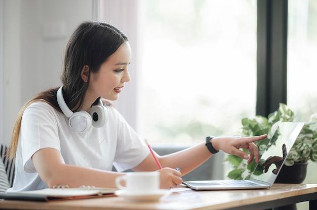Piękna azjatykcia kobieta pracuje z laptopem oblicza podczas gdy siedzący w żywym pokoju w domu.
