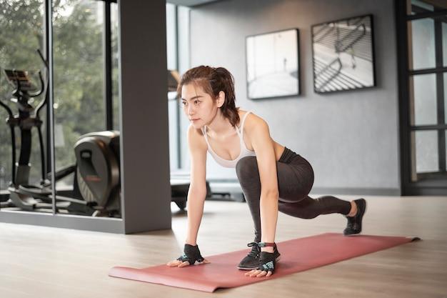 Piękna azjatykcia kobieta robi ćwiczeniu w gym