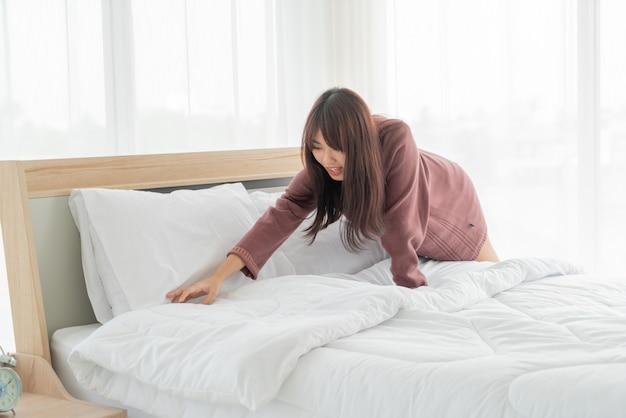 Piękna azjatykcia kobieta robi łóżku w pokoju z białym czystym prześcieradłem