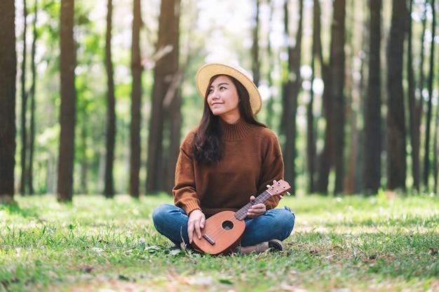 Piękna azjatykcia kobieta siedzi ukulele i bawić się w parku